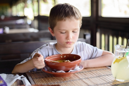 gastronome: 7 years old child, boy eating soup in restaurant