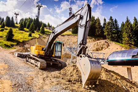 earthmover: Yellow excavator on tracks while working in the mountains Stock Photo