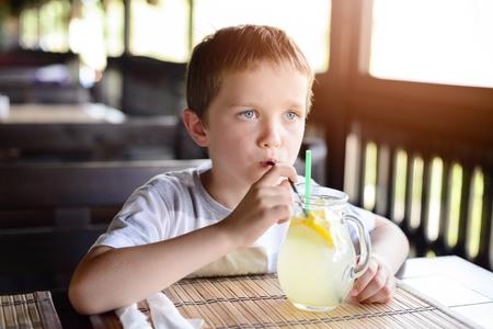 Little child boy enjoying his delicious lemonade in restaurant