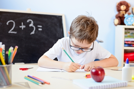 multiplication: 7 years old boy solves multiplication table in his copybook. Back to school
