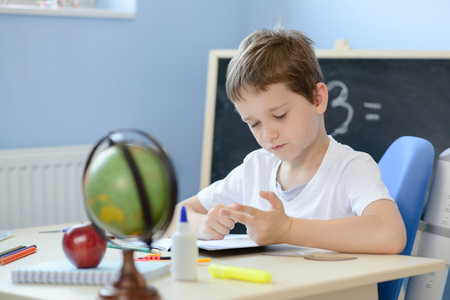 7 years old boy solves multiplication table in his copybook and counting on fingers. Back to school Standard-Bild