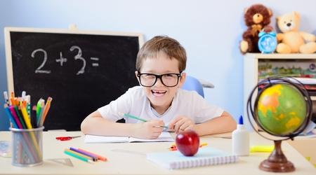 multiplicacion: niño de 7 años de edad resuelve tabla de multiplicar en su cuaderno. De vuelta a la escuela