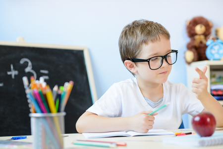 7 years old boy solves multiplication table in his copybook and counting on fingers. Back to school 스톡 콘텐츠