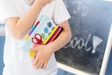 seven years: Happy seven years old boy holding his school supplies. Back to school Stock Photo