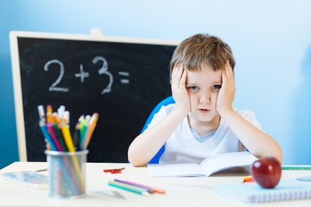 Seven years old boy, child thinking about homework solution. Back to school