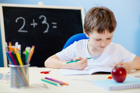seven years: Seven years old boy, child doing his homework. Back to school
