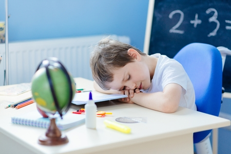 7 year old: Tired 7 year old boy fell asleep while doing homework Stock Photo