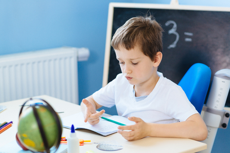 7 歳の少年、彼の宿題をしながら指でカウントします。学校に戻る 写真素材