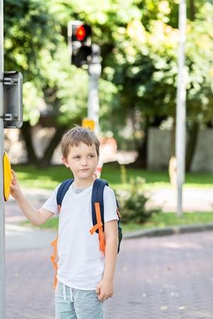 semaforo peatonal: Pequeño colegial con mochila pulsando un botón en los semáforos. Camino a la escuela
