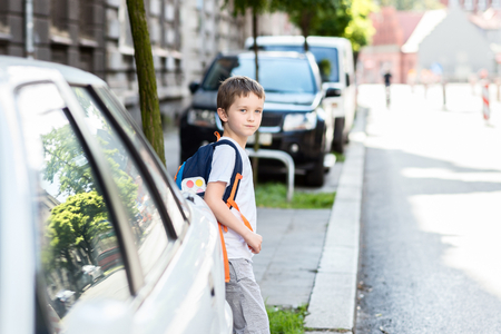 Little schoolboy waiting for the opportunity to move to the other side of the street. Road to school