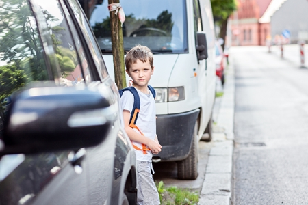 elementary schools: Little schoolboy waiting for the opportunity to move to the other side of the street. Road to school