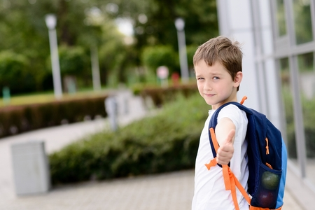 Happy little 7 years schoolboy going to school. Thumbs up. Dressed in white t shirt. Blue backpack Imagens