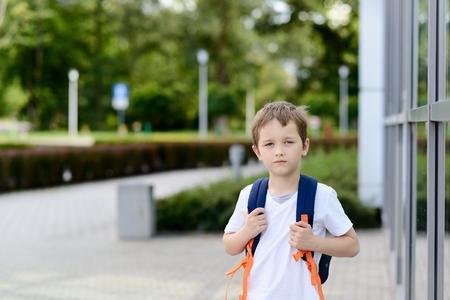 Little 7 years schoolboy going to school. Dressed in white t shirt . Blue backpack Reklamní fotografie