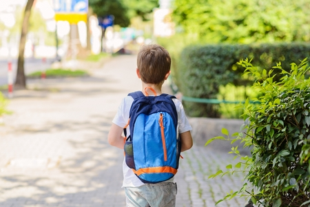 backpack: Little 7 years schoolboy going to school. Dressed in white t shirt and shorts. Blue backpack