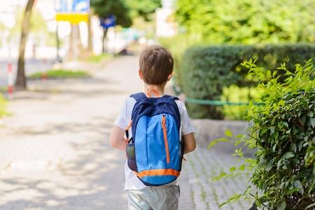 niños saliendo de la escuela: Poco 7 años colegial ir a la escuela. Vestido con la camiseta blanca y pantalones cortos. mochila azul