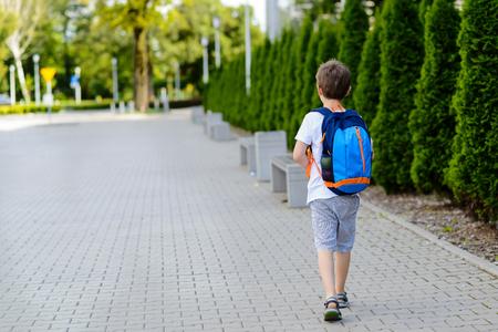 かわいい 7 歳の男子学生が学校に行きます。白い t シャツとショート パンツを着ています。ブルー バックパック 写真素材