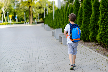 Little 7 years schoolboy going to school. Dressed in white t shirt and shorts. Blue backpack Stock Photo