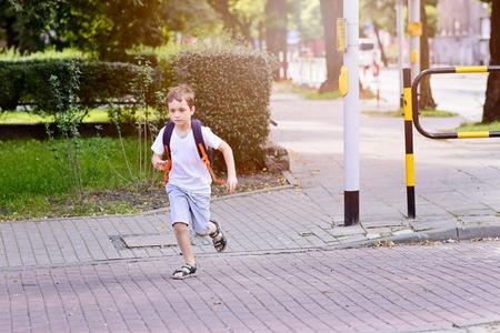かわいい 7 歳の男子学生が緑色の光を待っています。白い t シャツとショート パンツを着ています。ブルー バックパック 写真素材