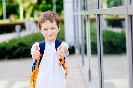 Happy little 7 years schoolboy showing thumbs up gesture. Dressed in white t shirt. Blue backpack