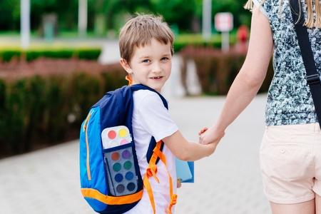 niño con mochila: El pequeño niño de 7 años con su madre en el camino a la escuela. Vestido con la camiseta blanca y pantalones cortos Foto de archivo
