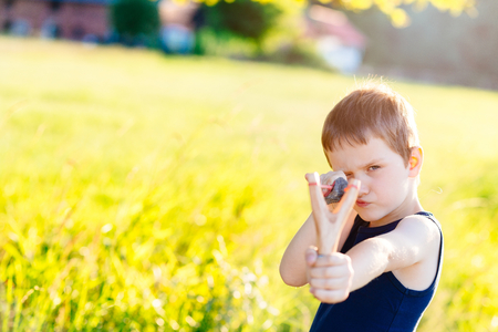 troublemaker: Little boy playing with slingshot at summer afternoon outdoors Stock Photo