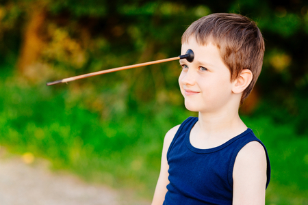 Little boy playing playing with bow and toy arrow at summer afternoon outdoors