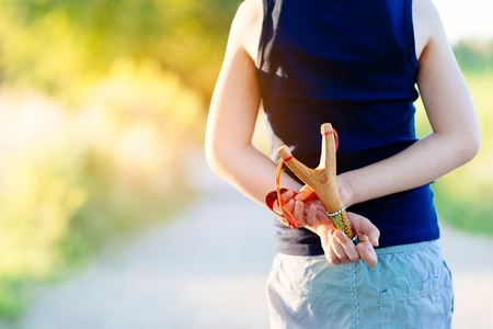 rowdy: Little boy playing with slingshot at summer afternoon outdoors Stock Photo