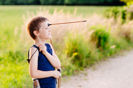 roughneck: Little boy playing playing with bow and toy arrow at summer afternoon outdoors