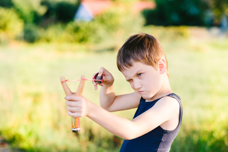 roughneck: Little boy playing with slingshot at summer afternoon outdoors Stock Photo