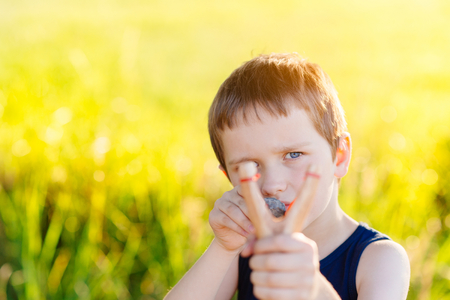 Little boy playing with slingshot at summer afternoon outdoors Stock Photo