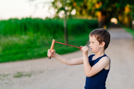 Little boy playing with slingshot at summer afternoon outdoors Reklamní fotografie