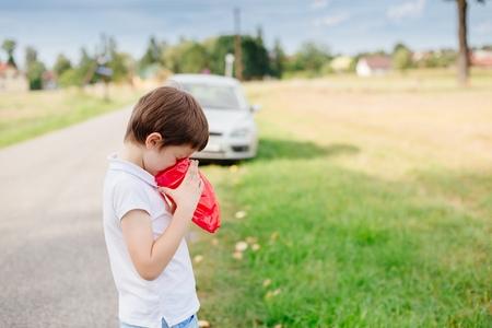 agotado: Siete años de edad hijo se sienta mal - sufre de la enfermedad de movimiento Foto de archivo