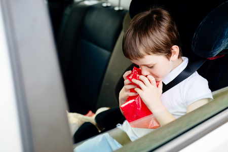 vómito: Seven years old child vomiting in car - suffers from motion sickness