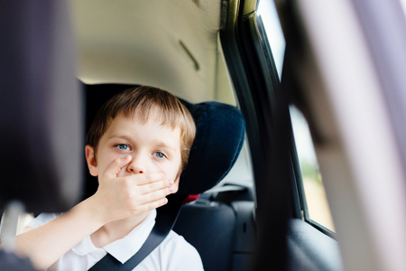 Seven years old small child in the backseat of a car sitting in children safety car seat covers his mouth with his hand - suffers from motion sickness