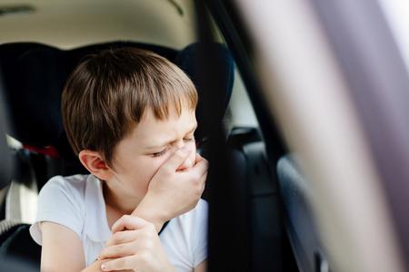 sept ans petit enfant sur la banquette arrière d'une voiture assis dans le siège de voiture de sécurité pour enfants couvre sa bouche avec sa main - souffre du mal des transports