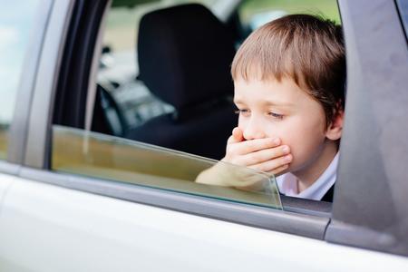 Siete años niño pequeño en el asiento trasero de un coche que se sienta en el asiento del coche de seguridad los niños cubre la boca con la mano - sufre de la enfermedad de movimiento