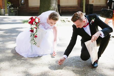 新婚夫婦は、結婚式のゲストによってスローされたコインを収集します。結婚式の日 写真素材