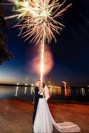 Jonggehuwden kussen in de buurt van het meer 's nachts. Vuurwerk boven hen. Trouwdag. bruiloft sessie