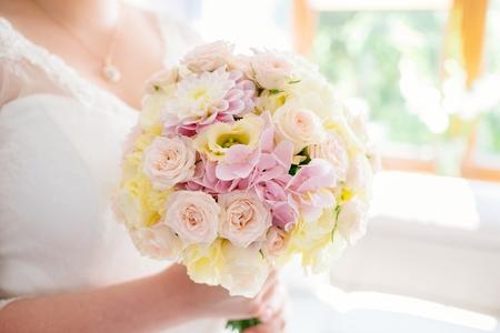 Mooie pastel bruiloft boeket in handen van de bruid. Wit en roze rozen