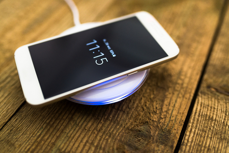 White smartphone charging on a charging pad. Wireless charging Banco de Imagens - 63663587