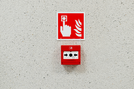 building wall: Red fire alarm button installed on the wall