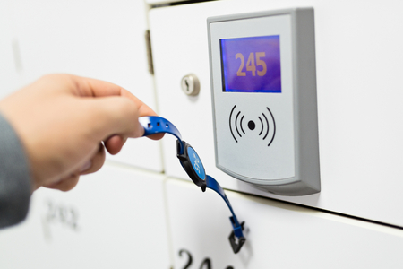 cardkey: Closeup on hand opening change room locker with watch shape electronic transponder. Safekeeping protection concept