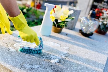 Een vrouw maakt het graf. Wassen grafsteen met borstel. De voorbereidingen voor Allerheiligen op 1 november Stockfoto