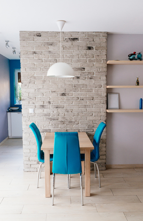 dining table and chairs: Modern dining room with wooden table, turquoise leather chairs, old empty grey brick wall and shelves