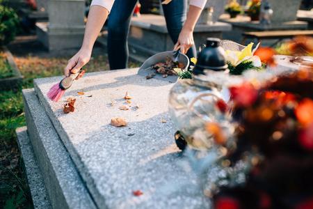 Eine Frau reinigt das Grab. Sweeps Blätter von dem Grabstein. Die Vorbereitungen für Allerheiligen am 1. November Standard-Bild - 63677617
