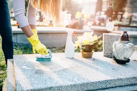 Een vrouw maakt het graf. Wassen grafsteen met borstel. De voorbereidingen voor Allerheiligen op 1 november