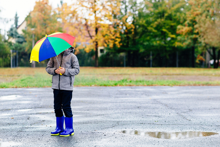 wellingtons: Sad child walking in rubber wellingtons on wet footpath. Rainy autumn day.