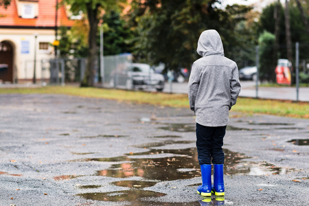 downcast: Sad little boy in rubber blue rain boots walking in the rain. Rainy autumn day