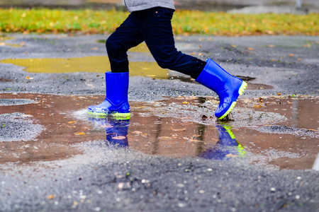 wellingtons: Happy little boy in rubber blue rainboots jumping to dirty puddle. Rainy autumn day Stock Photo