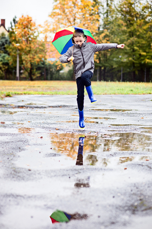 Happy little boy in rubber blue rainboots jumping to dirty puddle. Rainy autumn day Stock Photo